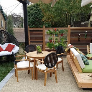 Design ideas for a small modern backyard patio in Kansas City with a vertical garden, decomposed granite and a pergola.