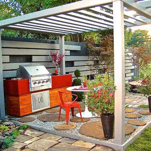 Esempio di un patio o portico etnico di medie dimensioni e dietro casa con ghiaia e una pergola