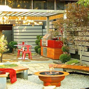 Esempio di un patio o portico etnico di medie dimensioni e dietro casa con un focolare, ghiaia e una pergola