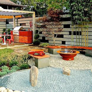 Idee per un patio o portico etnico dietro casa e di medie dimensioni con un focolare, ghiaia e una pergola