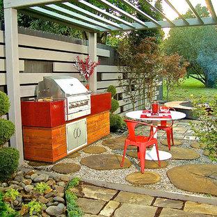 Ispirazione per un patio o portico etnico di medie dimensioni e dietro casa con ghiaia e una pergola