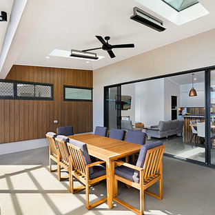 Inspiration for a mid-sized contemporary side yard patio in Other with tile and a roof extension.