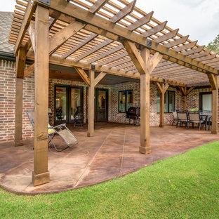 Idee per un patio o portico stile americano di medie dimensioni e dietro casa con cemento stampato e una pergola