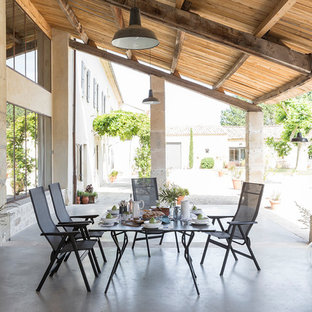 Tuscan backyard concrete patio photo in Lyon with a roof extension