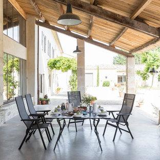 Idée de décoration pour une terrasse arrière méditerranéenne avec une dalle de béton et une extension de toiture.