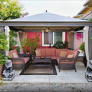 Ispirazione per un piccolo patio o portico etnico in cortile con cemento stampato e un gazebo o capanno