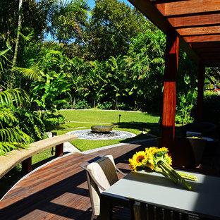 Ispirazione per un patio o portico etnico di medie dimensioni e dietro casa con un focolare, pedane e una pergola
