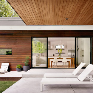 Mid-sized trendy backyard concrete patio photo in Austin with a roof extension