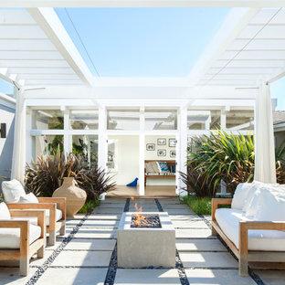 Esempio di un patio o portico contemporaneo dietro casa con un focolare, pavimentazioni in cemento e una pergola