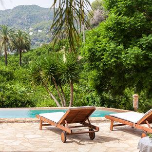 Diseño de piscina alargada, mediterránea, rectangular, en patio trasero, con adoquines de piedra natural