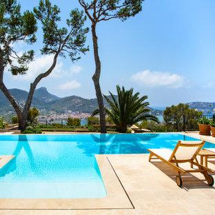 Foto de piscina infinita, mediterránea, grande, a medida, en patio trasero, con suelo de baldosas