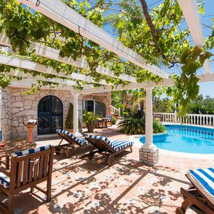 Ejemplo de casa de la piscina y piscina alargada, mediterránea, de tamaño medio, tipo riñón, en patio, con suelo de baldosas