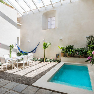 Ejemplo de piscina mediterránea, rectangular, en patio, con gravilla