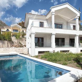 Imagen de casa de la piscina y piscina alargada, mediterránea, de tamaño medio, rectangular, en patio delantero