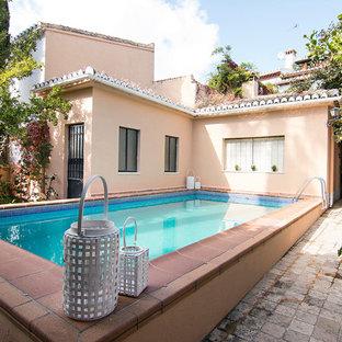 Diseño de piscina alargada, mediterránea, rectangular, en patio trasero, con adoquines de ladrillo