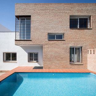 Ejemplo de piscina alargada, moderna, rectangular, en patio trasero, con suelo de baldosas