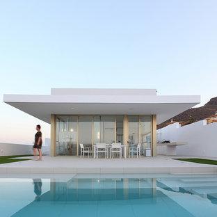 Ejemplo de casa de la piscina y piscina alargada, actual, de tamaño medio, a medida, en patio delantero, con suelo de baldosas