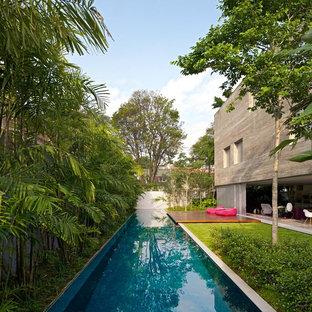 Imagen de casa de la piscina y piscina alargada, exótica, de tamaño medio, rectangular, en patio lateral