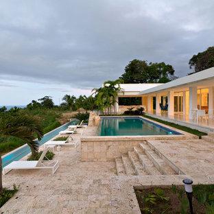 Ejemplo de piscina infinita, moderna, rectangular, con suelo de baldosas