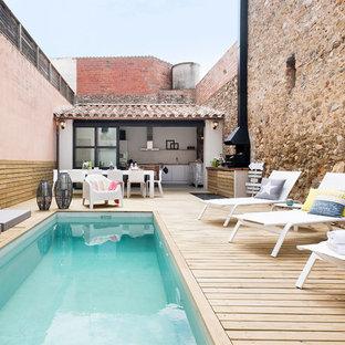 Foto de casa de la piscina y piscina alargada, mediterránea, de tamaño medio, rectangular, en patio trasero, con entablado