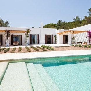 Foto de piscina alargada, mediterránea, de tamaño medio, rectangular, en patio trasero, con gravilla