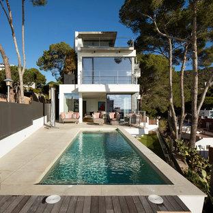 Imagen de casa de la piscina y piscina alargada, contemporánea, de tamaño medio, rectangular, en patio trasero, con suelo de baldosas