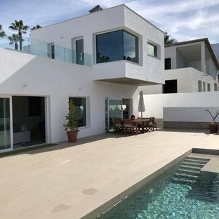 Modelo de piscina alargada, actual, pequeña, rectangular, en patio delantero, con privacidad y suelo de baldosas