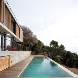 Photo of a large modern front yard rectangular aboveground pool in Other with a pool house and decking.
