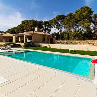Ejemplo de casa de la piscina y piscina alargada, rústica, grande, rectangular, en patio, con suelo de baldosas