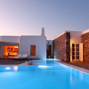 Diseño de piscina mediterránea, grande, en forma de L, en patio trasero