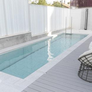 Modelo de casa de la piscina y piscina alargada, actual, de tamaño medio, rectangular, en patio delantero, con suelo de baldosas
