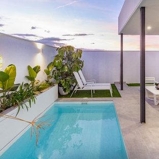 Foto de piscina actual, rectangular, con suelo de baldosas