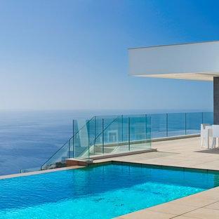 Ejemplo de piscinas y jacuzzis infinitos, marineros, rectangulares, en patio delantero, con suelo de baldosas
