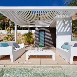 Modelo de casa de la piscina y piscina infinita, contemporánea, grande, a medida, en patio trasero, con suelo de baldosas
