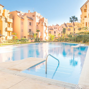Ejemplo de piscina infinita, costera, extra grande, a medida, en patio delantero, con granito descompuesto