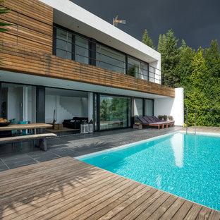 Imagen de piscina infinita, contemporánea, rectangular, en patio trasero, con entablado
