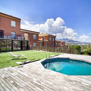 Ejemplo de casa de la piscina y piscina tradicional, pequeña, redondeada, en patio trasero, con entablado