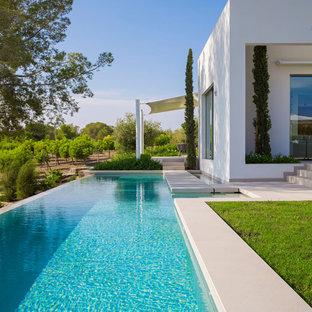 Modelo de casa de la piscina y piscina infinita, minimalista, de tamaño medio, rectangular, en patio lateral