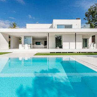 Foto de casa de la piscina y piscina alargada, actual, de tamaño medio, rectangular, en patio trasero, con losas de hormigón