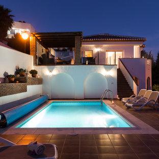 Modelo de piscina alargada, mediterránea, grande, rectangular, con adoquines de piedra natural