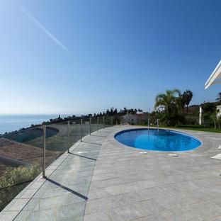 Ejemplo de piscina alargada, contemporánea, grande, redondeada, en azotea, con adoquines de ladrillo