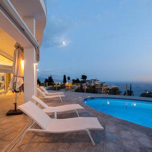Foto de piscina alargada, actual, grande, redondeada, en azotea, con adoquines de ladrillo