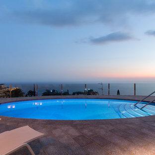 Imagen de piscina alargada, contemporánea, grande, redondeada, en azotea, con adoquines de ladrillo