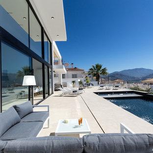 Foto de piscina infinita, contemporánea, grande, rectangular, en patio trasero, con granito descompuesto