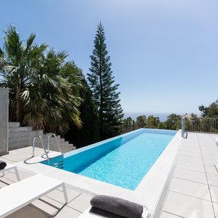 Ejemplo de piscina infinita, actual, rectangular, con adoquines de hormigón