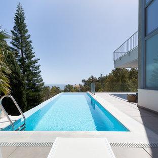 Imagen de piscina alargada, actual, rectangular, en patio trasero, con losas de hormigón