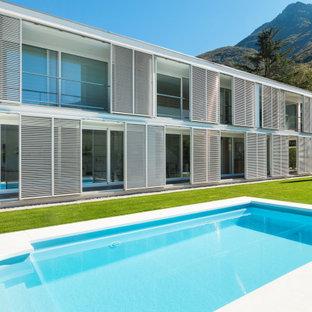 Diseño de piscina alargada, mediterránea, grande, rectangular, en patio delantero, con suelo de baldosas