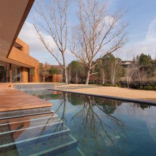 Diseño de casa de la piscina y piscina alargada, actual, de tamaño medio, rectangular, con entablado