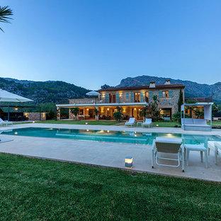 Imagen de piscina alargada, rural, grande, rectangular, en patio trasero, con suelo de baldosas