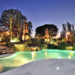 Diseño de piscina alargada, tropical, grande, a medida, con adoquines de hormigón